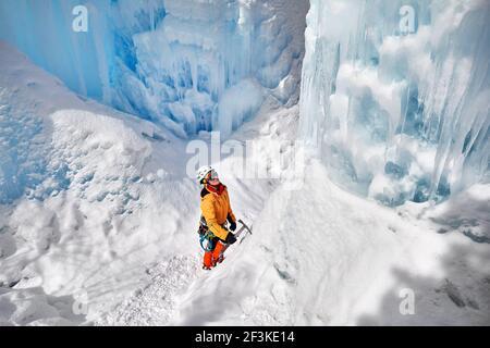 Woman climber in orange jacket with ice axe near frozen waterfall in the mountains in Almaty, Kazakhstan