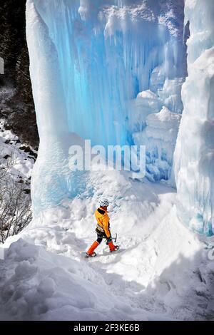 Woman climber in orange jacket with ice axe walking near frozen waterfall in the mountains in Almaty, Kazakhstan