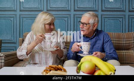 Mature family couple grandfather, grandmother relaxing on cozy sofa enjoying conversation at home