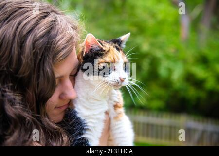 Closeup portrait of happy smiling young woman bonding holding in hands calico cat pet companion, bumping rubbing bunting heads, friends showing affect Stock Photo