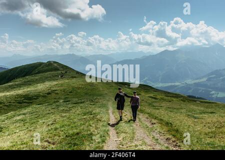 Man and woman backpackers trekking in Alps, Austria.Active healthy lifestyle.Couple in love walking together on peaks.Friends in mountains.Hiking Stock Photo