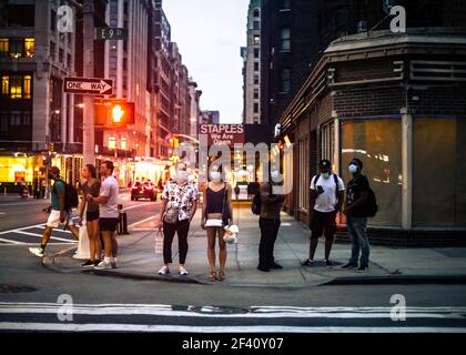 New York City, New York - August 18, 2020:  Street scene from Manhattan on a summer evening of people waiting to cross the street wearing masks during