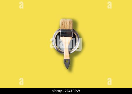 Demonstrating trendy Color of the Year 2021. Illuminating Yellow and Ultimate Gray. Brush and open paint can with on color background. Appartment