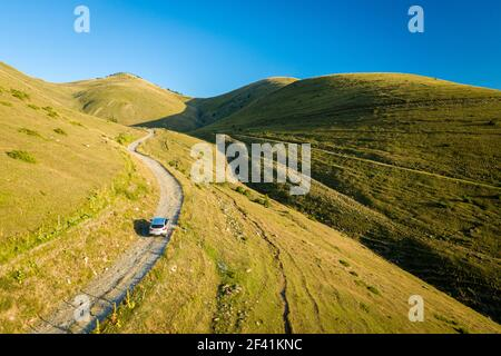 Back aerial view of SUV car driving up a mountain road on a grassy hill landscape