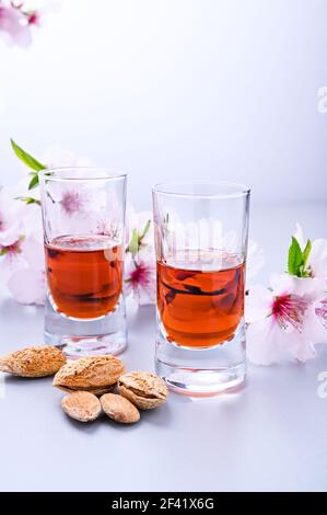 almond liquor. The traditional strong drink in italy to complete the dinner is a liqueur made from nuts and berries. Ratafia, alcohol in shot. on the table and blooming almonds. vertical . Copy space