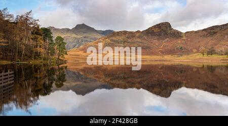 A panoramic long exposure of Blea Tarn the Langdale and side pikes  showing reflections of the surrounding woods and mountains in the clear calm tarn.