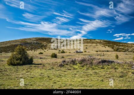 High arid causses landscape, cirrus clouds, view from road D16, at Causse Mejean plateau, Massif Central, Lozere department, Occitanie region, France