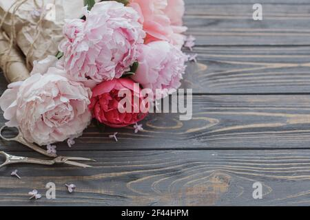 Beautiful stylish peony bouquet in paper, twine and scissors on rustic dark wooden background, copy space. Happy Mothers day greetings. Pink and white