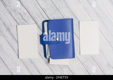 blue business card holder with letterheads on a wooden table top view
