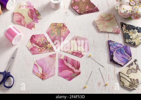 Pentagonal pieces of fabric lying in the shape of a flower, stacks of multi-colored pieces of fabric, sewing accessories on a white surface