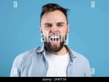 Enraged bearded guy shouting in anger, expressing his aggression over blue studio background