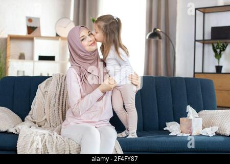 Muslim family mom and child. Cute little girl, kissing her smilin mom in hijab in cheek with love. Happy young Arabian mother having fun with her child girl, spending free time at home.