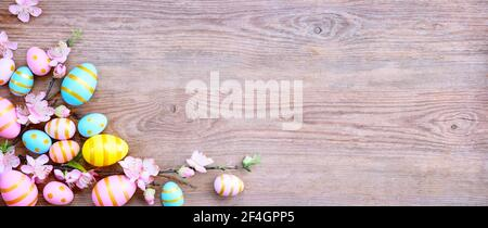 Happy Easter background with pink; yellow, blue eggs and beautiful spring flowers on wooden table. Gift card with colorful easter eggs on old wooden t