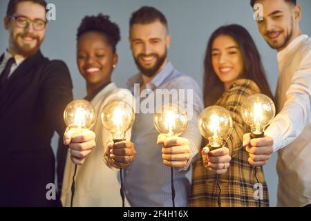 Group of happy creative young diverse business people holding shining light bulbs