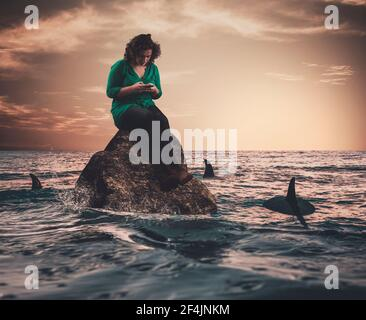 Young woman on a rock in the sea surrounded by sharks .Careless sitting on rock  under threat.