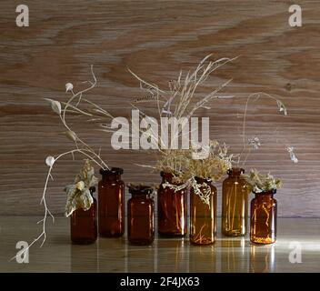 Glass dark bottles with dried herbs with seeds. On a wooden background, in yellow beige tones, the view from the front is consecrated by a ray. Stock Photo