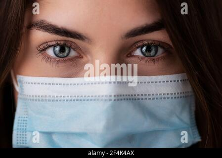 Head shot of young woman with beautiful green eyes wearing surgical face mask. Studio shot. Isolated background. - Stock Photo