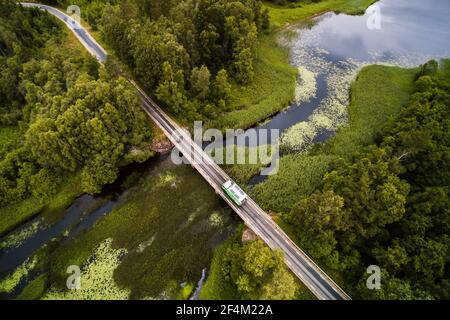 Drone POV of a camper van crossing a bridge over a river, Sweden Stock Photo