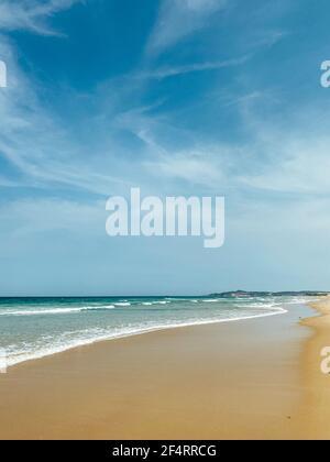 Tropical vacation concept. Soft long waves on the tropical shore of a long empty sea beach. Sandy oceanic beach. Sea foam on the Caribbean coast