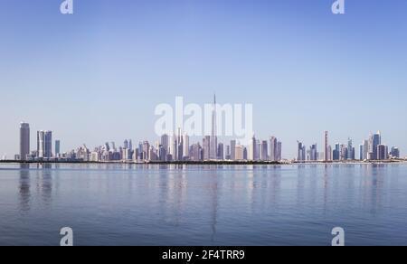 Dubai Downtown skyline panorama with reflections in Dubai Creek, cold colors, seen from Dubai Creek Harbour promenade.