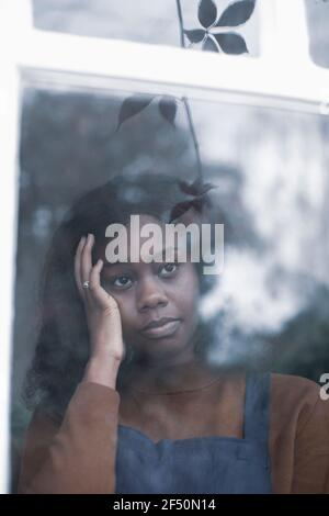 Sad young woman with head in hands looking out window