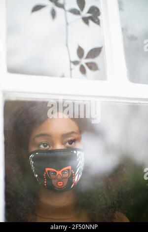 Thoughtful woman in face mask at window