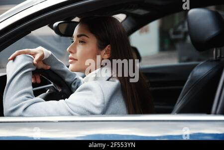 Elegant businesswoman sitting in her car and waiting for someone, looking at city street. Woman driver looking thoughtful out of window