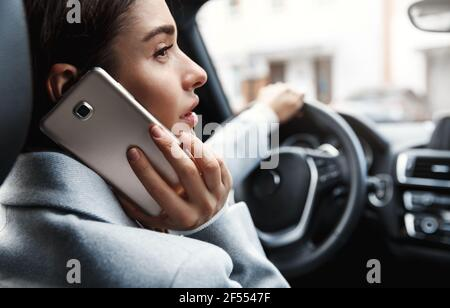 Close-up of young businesswoman driving to office and calling someone on phone. Woman sitting on driver sit and talking on smartphone