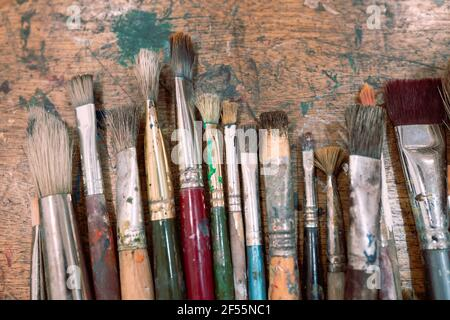 Variety of messy paintbrushes on table Stock Photo