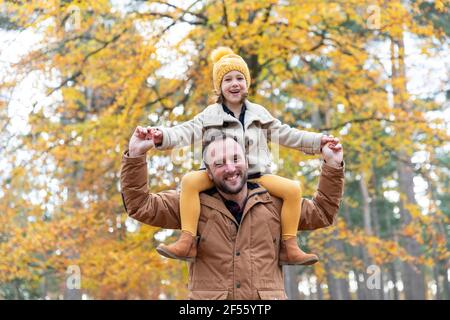 Playful father carrying smiling daughter while standing in forest