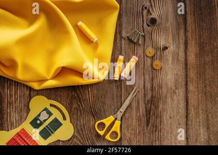 Sewing accessories and yellow fabric on wooden table. Sewing threads, needles, pins, buttons and scissors. Top view, flat lay concept. Accessories
