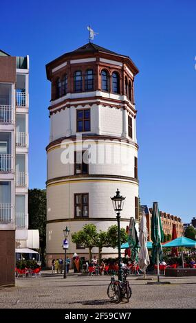 The ancient Schlossturm in Old Town Düsseldorf with people sitting in outdoor café restaurant. - Stock Photo