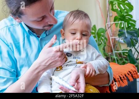 Father rubbing pain relieving gel into his little baby boy's growing teeth or gums. Baby healthcare concept.