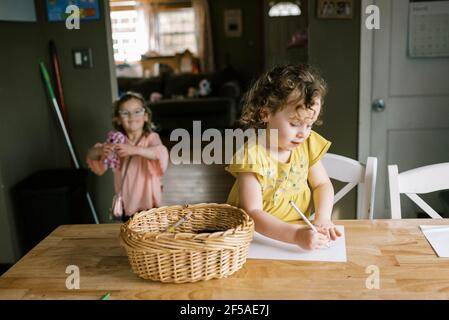 twin toddler girls spending time together in kitchen while coloring