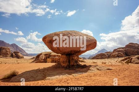 Mushroom shaped rock at Wadi Rum desert, bright sun shines on mountains background