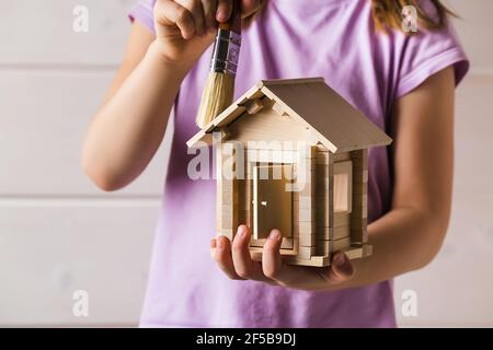 Child hands with toy wooden house and paint brush, home services concept
