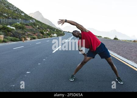 African american man exercising outdoors stretching on a coastal road