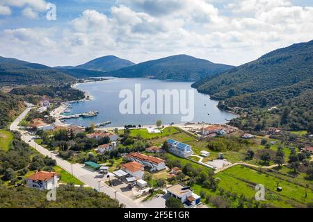 Top drone view from above to fairytale hills valley with round blue lake, red roof tiles country houses, summer green gardens, white clouds, sunny sky - Stock Photo