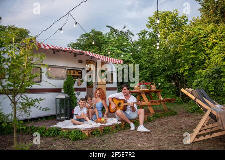 Young father plays the guitar, red-haired mother with children sing songs. Happy Family on picnic, camping by trailer truck in nature outside the city