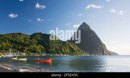 Soufriere, St Lucia. View from sandy beach across Soufriere Bay to Petit Piton, evening, fishermen in colourful boat at water's edge.