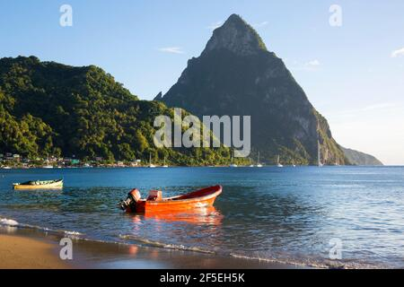 Soufriere, St Lucia. View from sandy beach across Soufriere Bay to Petit Piton, evening, colourful fishing boat moored at water's edge.