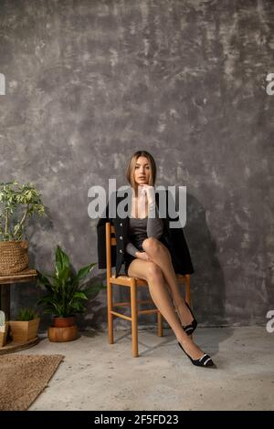 Young beautiful slender business woman designer architect student sits on wicker chair against background of concrete wall and floor, wooden furniture