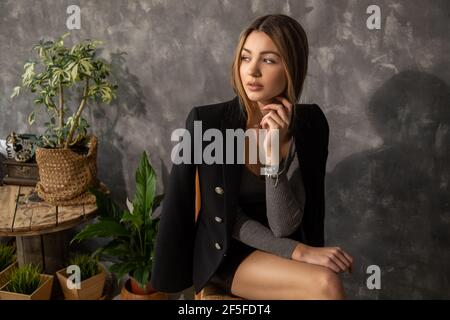 Photo of Young beautiful business woman designer architect student sits on chair against background of concrete wall, wooden furniture, plant green