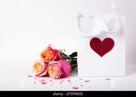 Roses and present gift in paper pack with red heart on white background/ Valentines day background