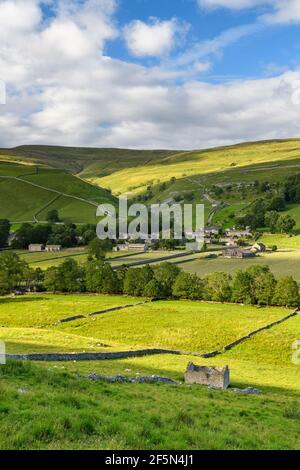 Picturesque Dales village houses, nestling in sunlit valley, fields, hills, hillsides, field walls & old barn ruin - Starbotton, Yorkshire England UK.