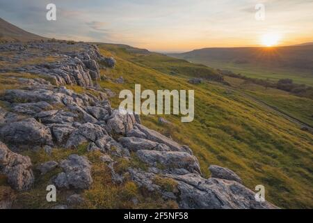 Sunrise or sunset golden light over the beautiful countryside landscape of limestone pavement and moorland at Southerscales in the Yorkshire Dales Nat