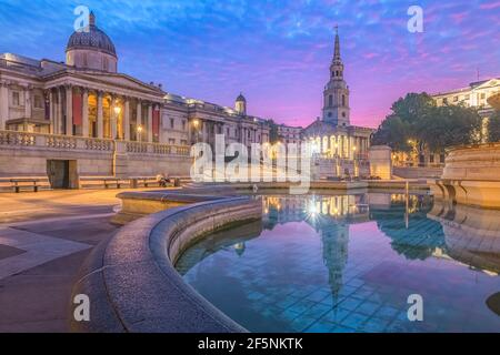 Night cityscape with a colourful, dramatic sky at sunrise or sunset at Trafalgar Square and the National Gallery in central London, UK.