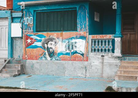 Baracoa, Cuba - October 25, 2019: Graffiti and wall painting representing the Cuban national hero Camilo Cienfuegos