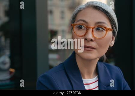 Close up portrait of pensive mature businesswoman looking away. Beautiful middle aged woman wearing eyeglasses standing outdoors. Vision concept