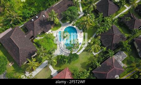 Amazing Luxury resort in Indonesia. Drone View of large villa with massive beautiful pool tucked within lush greenery and perched on a cliff in Nua - Stock Photo